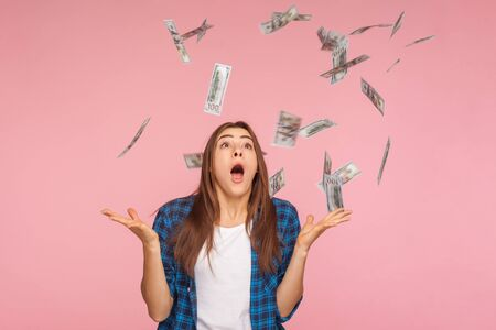 Money rain. Shocked excited girl in checkered shirt shouting in amazement and looking up at dollars falling on her, surprised by unexpected lottery win, big salary. indoor studio shot, pink background