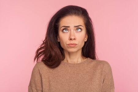 Portrait of awkward funny young woman with brunette hair making silly comical face with eyes crossed, thinking intensely looking dumb and confused. indoor studio shot isolated on pink background