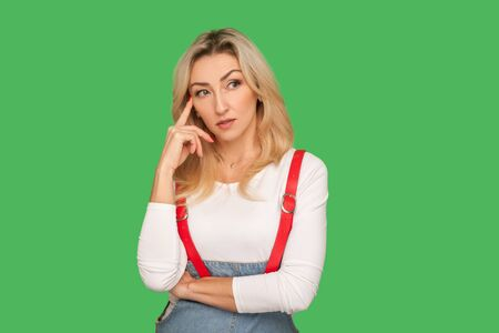 Let's think! Portrait of smart pensive adult woman in stylish overalls touching temple while thinking intensely, musing and pondering clever solution. indoor studio shot isolated on green background