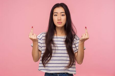 Portrait of annoyed rude vulgar girl with long brunette hair showing fuck off sign, expressing negativity disrespect and hate with middle finger gesture. indoor studio shot isolated on pink background