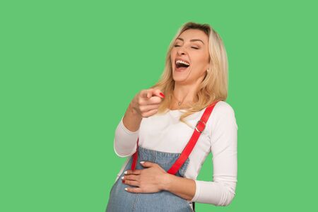 Ha ha ha, look at you! Portrait of adult woman bursting into laughing while watching someone really funny and ridiculous, pointing finger to camera. indoor studio shot isolated on green background Foto de archivo