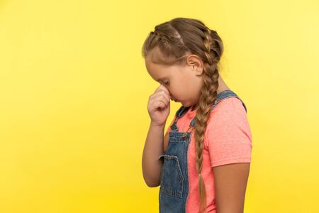 Side view of unhappy little girl with braid in denim overalls hiding face down and crying, upset about loss or defeat, child feeling sorrow and regret. indoor studio shot isolated on yellow background