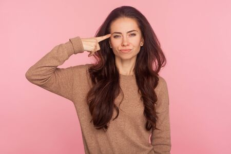 This is insane! Portrait of displeased woman annoyed with dumb idea showing stupid gesture, blaming some idiot for crazy cuckoo mind, silly senseless talk. studio shot isolated on pink background