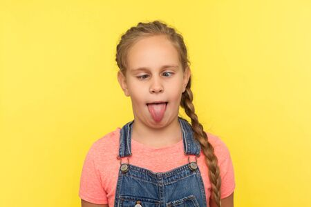 Portrait of adorable funny little girl in denim overalls fooling around, making dumb face with crossed eyes and sticking out tongue, looking silly stupid. studio shot isolated on yellow background
