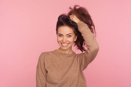 Portrait of attractive young woman in pullover making ponytail with long brown hair and smiling at camera, shampoo and hair treatment, beauty care. indoor studio shot isolated on pink background Stockfoto