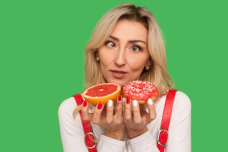Closeup of confused adult woman looking with crossed eyes at grapefruit and doughnut, expressing doubts, choosing confectionery vs healthy fruit. indoor studio shot isolated on green background