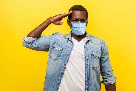 Portrait of serious confident man in denim casual shirt with surgical medical mask standing as soldier giving salute, ready for order. indoor studio shot isolated on yellow background Archivio Fotografico