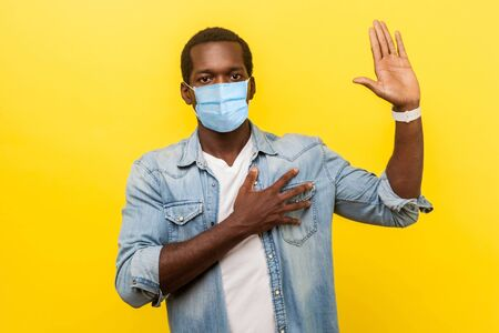 Portrait of honest serious man in denim casual shirt with surgical medical mask keeping hand on chest, raising palm, giving promise, pledge. indoor studio shot isolated on yellow background