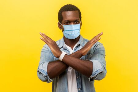 Portrait of absolutely convinced man i with surgical medical mask standing crossing hands, showing x sign meaning stop, there is no way, finish. indoor studio shot isolated on yellow background