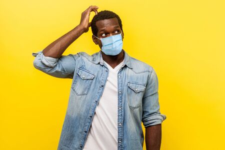 Portrait of uncertain young man with surgical medical mask looking up, scratching head while thinking with confused puzzled face. indoor studio shot isolated on yellow background