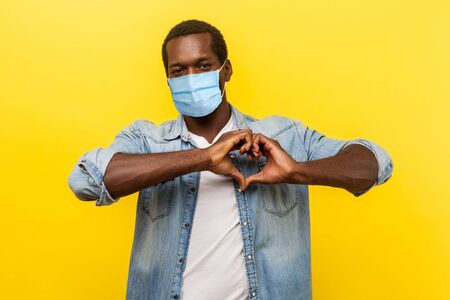Portrait of handsome cheerful man with surgical medical mask making heart shape with hands, expressing love feelings or friendship. indoor studio shot isolated on yellow background