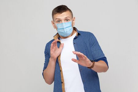 No, wait. Portrait of scared young man in casual style with surgical medical mask standing and looking at camera, afraid and panic. indoor studio shot, isolated on gray background.