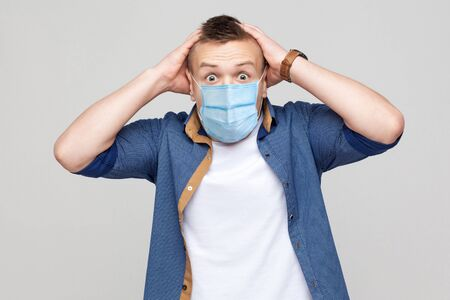 Oh my God. Portrait of shocked young man in casual style with surgical medical mask standing, holding head and looking at camera with unbelievable face. indoor studio shot, isolated on gray background