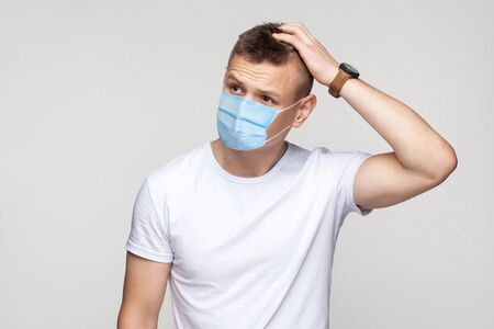 Let me think. Portrait of thoughtful young man in white shirt with surgical medical mask standing, scratching his head and thinking what to do. indoor studio shot, isolated on gray background.