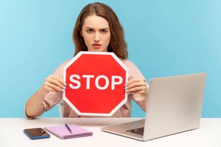 Interdit, accès interdit ! Jeune femme tenant un symbole d'arrêt, avertissant avec un panneau de signalisation rouge et regardant avec colère, assise sur le lieu de travail avec un ordinateur portable, bureau à domicile. tourné en studio intérieur isolé sur fond bleu Banque d'images