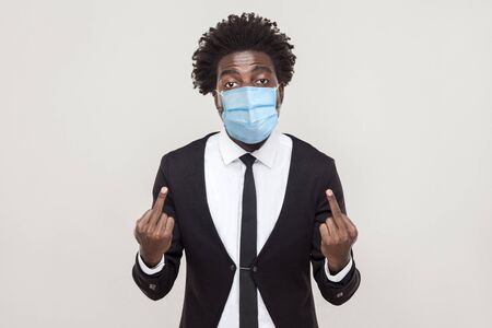 Portrait of angry young man wearing black suit with medical mask standing and looking with aggressive face and showing middle finger. indoor studio shot isolated on gray background.