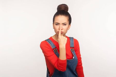 Portrait of girl with hair bun in overalls pointing nose doing lie gesture, suspecting trickster in falsehood, her look expressing distrust, disbelief. indoor studio shot isolated on white background