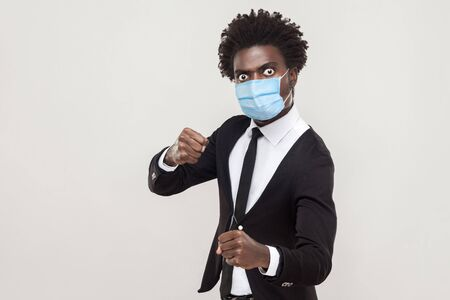Portrait of angry man wearing black suit with surgical medical mask standing with boxing fists and ready to attack or defense. indoor studio shot isolated on gray background.