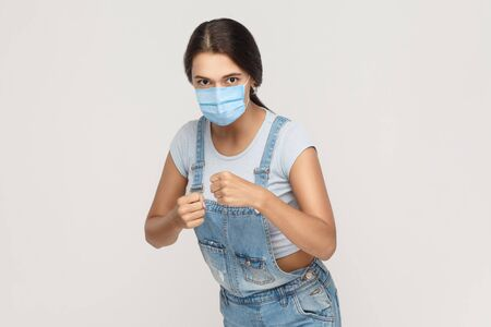 Portrait of angry mad young brunette woman with medical mask in denim overalls standing with boxing fists, looking and ready to attack or defence. indoor studio shot isolated on gray background. Фото со стока