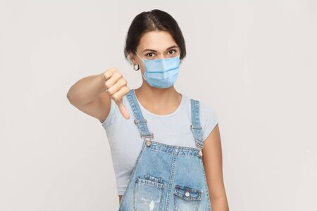 I don't like it. Portrait of dissatisfied young brunette woman with surgical medical mask in denim overalls standing thumbs down and looking at camera. indoor studio shot isolated on gray background. Banco de Imagens