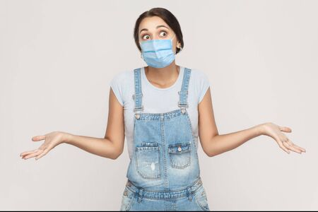 I don't know. Portrait of thoughtful young brunette woman with surgical medical mask in denim overalls standing raised arms and looking away. indoor studio shot isolated on gray background.