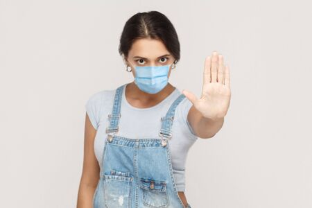 Stop. Portrait of angry young brunette woman with surgical medical mask in denim overalls standing and showing stop sign with hands, looking at camera. indoor studio shot isolated on gray background.