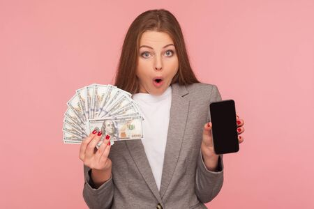 Apply online, loan application. Portrait of amazed businesswoman in suit jacket holding dollar banknotes and cellphone, shocked by mobile banking. indoor studio shot isolated on pink background