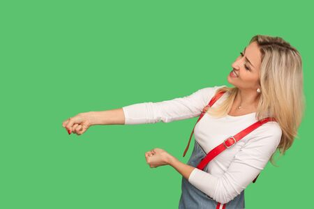 Portrait of persistent adult woman in denim overalls pulling invisible rope with great effort, being purposeful, using all strength and energy to achieve goal. studio shot isolated on green background