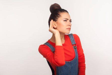 Portrait of attentive girl with hair bun in denim overalls holding hand near ear listening to gossip, silent talk, confidential information. indoor studio shot, white background 版權商用圖片