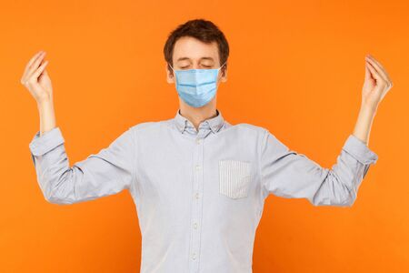Yoga and meditation. Portrait of calm young worker man with surgical medical mask standing with closed eyes and meditating. indoor studio shot isolated on orange background. Stock Photo