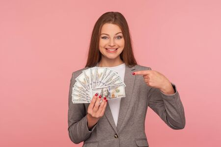 Look, I am rich! Portrait of wealthy elegant woman in suit jacket holding dollar banknotes and smiling to camera, enjoying business profit, income. indoor studio shot isolated on pink background Imagens
