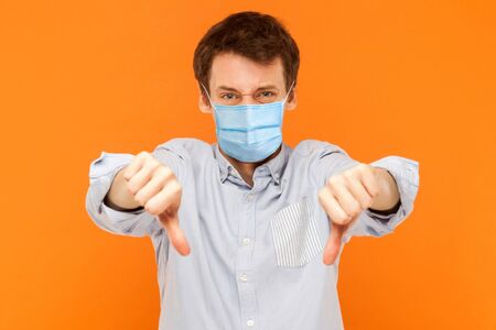 I don't like it. Portrait of sad young worker man with surgical medical mask standing thumbs down and looking at camera with dissatisfied face. indoor studio shot isolated on orange background.