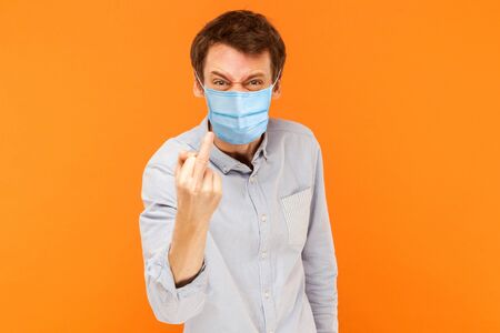 Portrait of angry young worker man with surgical medical mask standing looking at camera with middle finger and aggressive face. indoor studio shot isolated on orange background. Stock fotó