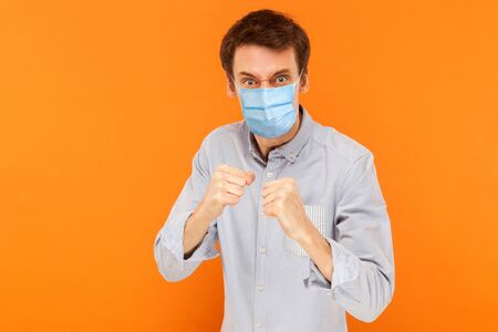 Portrait of angry young worker man with surgical medical mask standing in boxing fists and looking at camera and ready to attack against virus. indoor studio shot isolated on orange background.