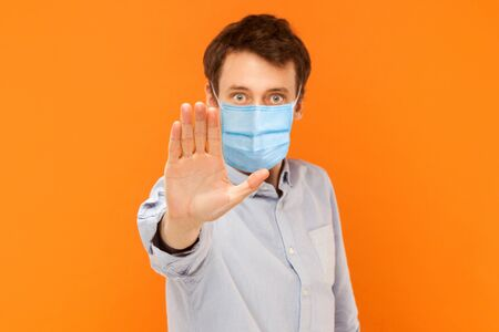 Stop! keep your distance. Portrait of angry or aggressive young worker man with surgical medical mask standing with stop hand and looking at camera. indoor studio shot isolated on orange background. Stock Photo