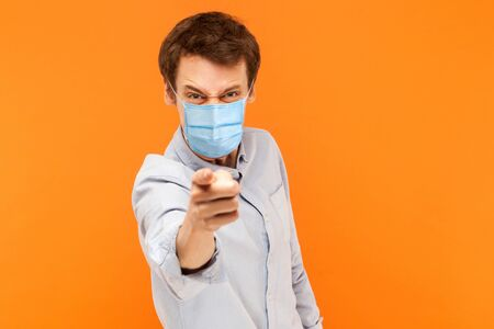 Hey you. Portrait of angry young worker man with surgical medical mask standing pointing and scolding at camera with mad face. indoor studio shot isolated on orange background.