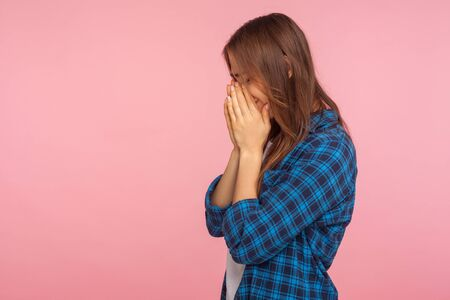 Side view of frustrated girl in checkered shirt holding head down and crying from depression, wiping tears, coping with grief and loss, feeling hopeless. indoor studio shot isolated on pink background