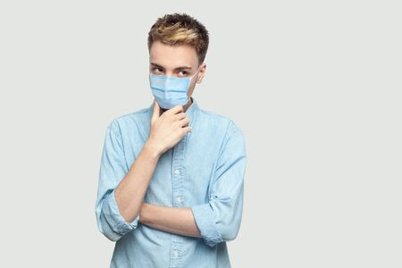 Portrait of thoughtful handsome young man with surgical medical mask in light blue shirt standing, holding his chin, thinking and looking away. indoor studio shot on grey background copy space.