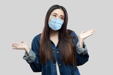 Confused beautiful brunette asian young woman with surgical medical mask in blue denim jacket standing raised arms and looking away thoughtful. studio shot, isolated on grey background.