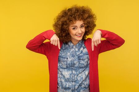 Look below, nice advertise here! Portrait of happy pretty curly-haired woman pointing down and smiling charming, showing place for commercial text, recommendation to subscribe. studio shot, isolated Stockfoto