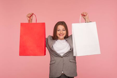 Portrait of attractive woman in business suit raising shopping bags and looking with joyful expression, smiling, satisfied with favorable purchase, discounts. studio shot isolated on pink background