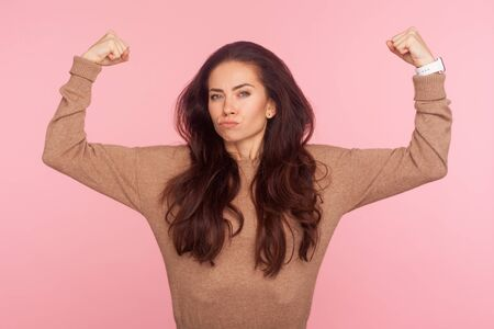 Concept of female power and independence. Confident brave young woman with brunette hair in pullover raising hands showing biceps, expressing strength. indoor studio shot isolated on pink background