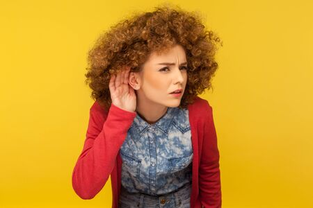 What are you saying? Portrait of woman with curly hair holding hand near ear and listening carefully intently, curious to hear secret quiet talk. indoor studio shot isolated on yellow background