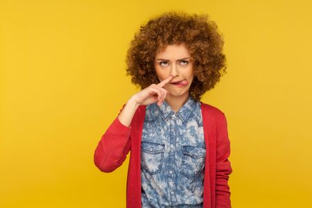 Portrait of funny woman with fluffy curly hair drilling nose fooling around, showing tongue out and picking nose with comical silly expression. indoor studio shot isolated on yellow background