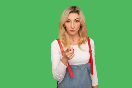 Hey, I'm warning you! Portrait of displeased angry adult blond woman in stylish denim overalls accusing with admonishing finger gesture, looking strict with dispraise. indoor studio shot, isolated Stock Photo