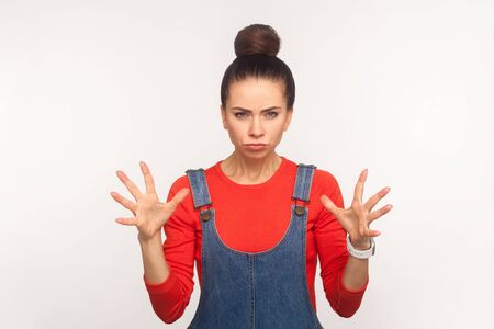 Portrait of irritated annoyed stressed girl with hair bun in denim overalls standing with clenched teeth and raised hands, expressing anger, aggression. indoor studio shot isolated on white background