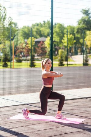 Full length, girl with athletic body in tight pants training on mat outdoor summer day, practicing split squats with raised hands, doing aerobics or pilates exercise. Sports activity for weight loss Фото со стока