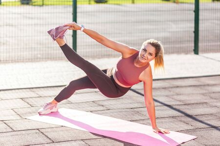 Fit sportive girl in tight pants training on mat outdoor summer day, standing plank pose on one hand and touching toe, practicing strength, doing aerobics pilates workout, Health care, sports activity Archivio Fotografico