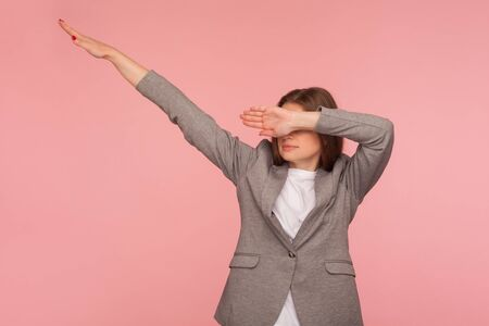 Portrait of successful young woman in business suit showing dab dance pose, famous internet meme of triumph, performing dabbing trends with hand gesture. studio shot isolated on pink background