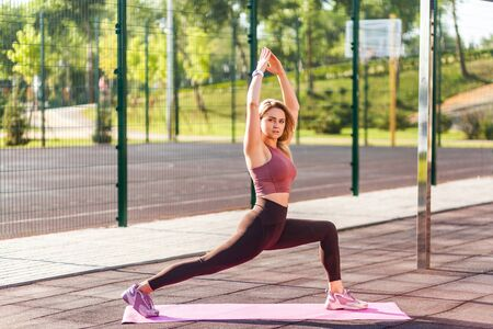 Motivated fit athletic woman in tight pants practicing yoga on mat outdoor summer day, standing in Virabhadrasana warrior pose and meditating, doing stretching exercise. Health care, sport activity